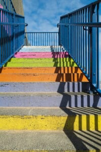 Concrete steps painted bright rainbow colours with a blue railing and a strong shadow pattern