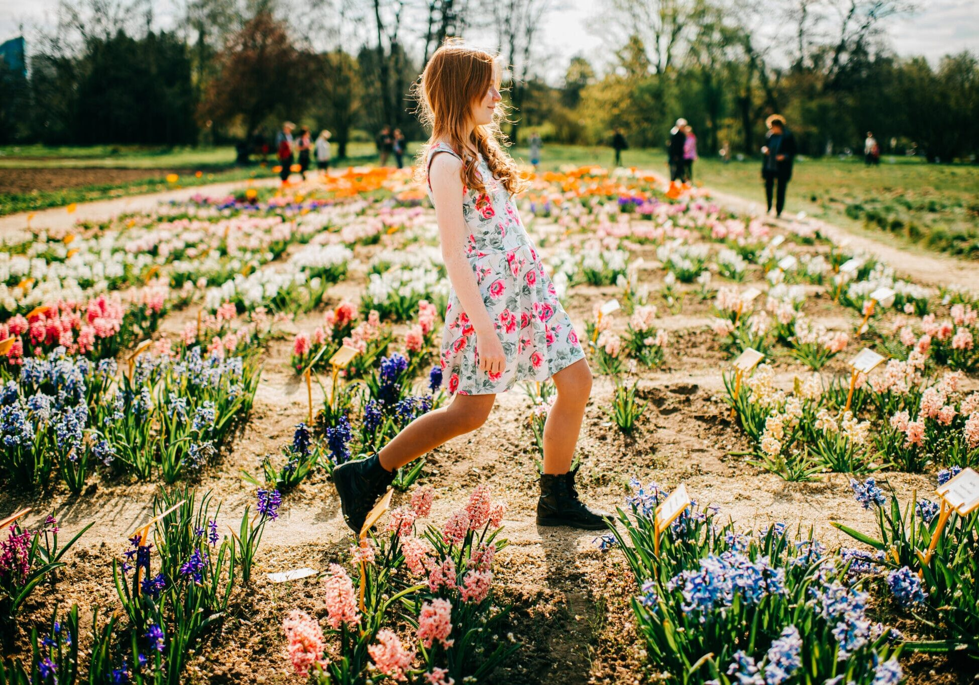 Cheerful young caucasian girl with long red hair and pale skin in flowers dress enjoys of the big flower garden.